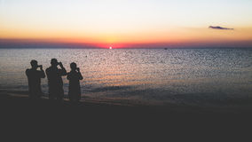 Three silhouettes on the beach at sunrise royalty free stock photo