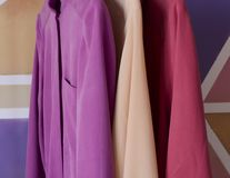 Three silk dresses hung on an offinger in the colors of magenta, fuchsia, violet, pink, poweder pink, peach pink, coral pink, rose stock photos