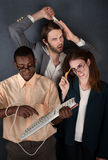 Three Silly Young People. Man and cross-eyed woman work while handsome man combs his hair Stock Photos