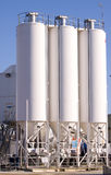 Three silos. Three sunlit silos on an industrial complex Stock Image