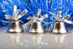 Three silver bells. On the background of blue garland Stock Image