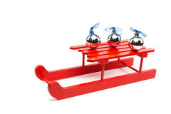Three silver christmas balls on red sledge. Silver christmas baubles and red sleigh isolated on black background Royalty Free Stock Image