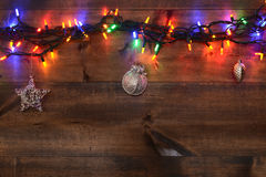 Three silver ornaments and christmas lights Stock Photos
