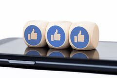 Three simple dice with Facebook like icons laying on a modern smartphone screen. Social media engagement concept
