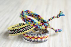 Three simple handmade homemade natural woven bracelets of friendship on white wooden table royalty free stock photos