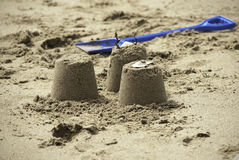 Three Simple Sandcastles with blue spade. 3 small simple sandcastles on a sandy beach with blue spade Stock Photo