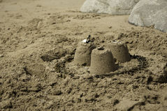 Three Simple Sandcastles. 3 small simple sandcastles on a sandy beach with large boulders Stock Photography