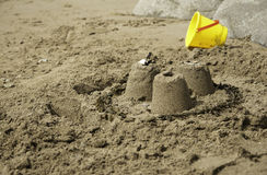 Three Simple Sandcastles with yellow bucket. 3 small simple sandcastles on a sandy beach with blue spade Royalty Free Stock Image