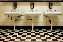 Three Sinks in Old Public Restroom. Three white porcelain sinks in an old Art Deco public bathroom with a black and white checkered tile floor stock photography