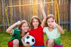 Three sister girls friends soccer football winner players. On the backyard Stock Photo