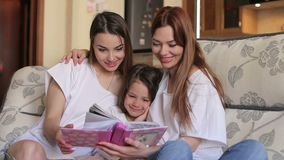 Three sister, two adults and one a small, look photo album sitting on couch. A young mother with a small daughter and an older sister watching a photo album at stock video footage