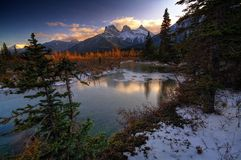 Three Sisters. In Canmore over a quiet section of the Bow River. Fall, first snow Stock Photography