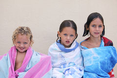 Three sisters. Three caucasian sisters with blue eyes wrapped up in a beach towel all with different expressions on their faces Royalty Free Stock Image