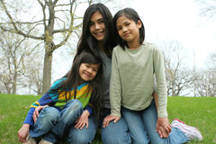 Three sisters. Sitting on grassy hilltop. Part Scandinavian, Thai heritage Stock Images