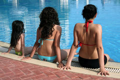 Three sisters. Three girls sitting by the pool Royalty Free Stock Photo