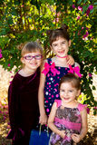 Three Sisters By Bougainvillea. Three young sisters pose for a picture in front of a bougainvillea bush.  They are ready to go to a party and the oldest is Royalty Free Stock Photos