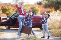 Three little girls traveling by car on a country road in the nature in summer stock photography