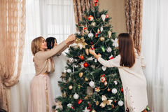 Three sisters decorate the Christmas tree Stock Images