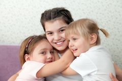 Three sisters  in   embrace on   couch royalty free stock photography