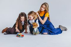 Three sisters having fun. Togertherness and friendship. Girls in long old fashioned dresses. Taking care of the youngest. Three sisters having fun. Girls in long stock photo