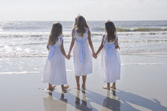 Three Sisters Holding Hands. Three young girls wearing matching white dresses, looking out at the ocean at the beach Royalty Free Stock Photos