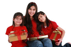 Three sisters holding presents. Three sisters wearing red shirts holding presents Royalty Free Stock Images