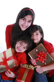 Three sisters holding presents. Three sisters wearing red shirts holding presents Stock Photography
