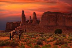 Three Sisters and a horse in Monument Valley Tribal Park, Arizona USA royalty free stock image