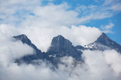 Three Sisters mountain range. The Three Sisters mountain range surrounded by morning clouds. Near Canmore in the Rocky Mountains of Canada Stock Photo