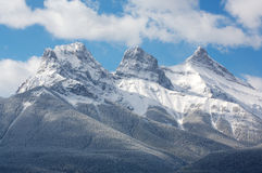 Three Sisters mountain range. The Three Sisters mountain range surrounded by morning clouds. Near Canmore in the Rocky Mountains of Canada Royalty Free Stock Images