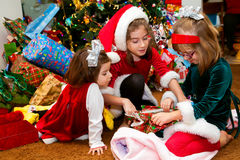 Three Sisters Opening Christmas Presents. Three sisters in Christmas dresses sit in a circle opening a present.  They are in front of a Christmas tree that is Royalty Free Stock Photo