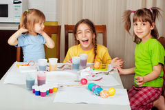 Three sisters painting on Easter eggs Stock Photography