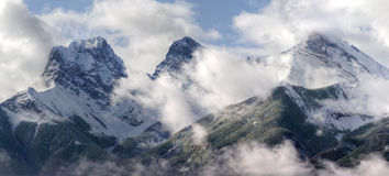 Three Sisters peeking through the clouds. Three Sisters - part of Canadian Rocky Mountains in Banff National Park, partialy covered with clouds on a chilly Stock Photos