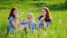 Three sisters playing on a green meadow with soap bubbles. Have fun together, happy childhood stock video