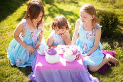 Three sisters playing tea party outdoors Royalty Free Stock Image