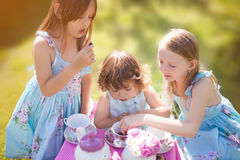 Three sisters playing tea party outdoors Royalty Free Stock Images