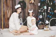 Three sisters posing in front of Christmas tree Stock Images