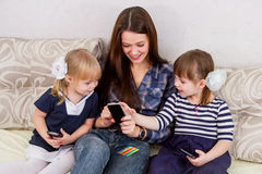 Three sisters with smartphones Royalty Free Stock Image