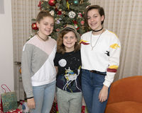 Three sisters standing in front of a Christmas tree Royalty Free Stock Images