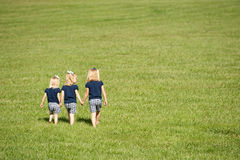 Three sisters walking in a field royalty free stock image