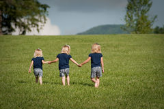 Three sisters walking in a field royalty free stock images