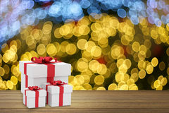 Three size of white square gift box with red ribbon bow put on wooden table against blurred out of focus bokeh background. Copy space for add your text.gift for Stock Image