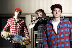 Three skateboarders in stylish pose Stock Photography