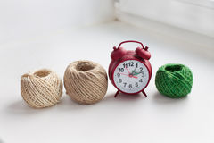 Three skeins of thread and red clock in a row. On the windowsill stock photography