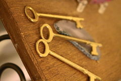 Three Skeleton Keys. Gold skeleton keys sitting on a worn old wooden shelf with a geode Royalty Free Stock Photography