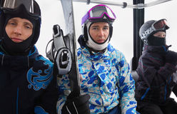 Three skiers in helmets ride on funicular royalty free stock image