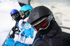 Three skiers ride on funicular in mountains Royalty Free Stock Image