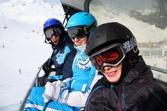 Three skiers ride on funicular in mountains Stock Images