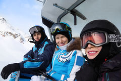 Three skiers ride on funicular in mountains Royalty Free Stock Photos
