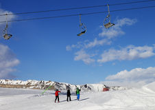 Three skiers on slope at sun nice day Royalty Free Stock Image